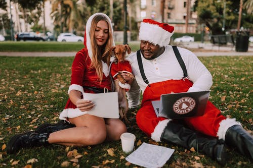 People And Dog in Santa Costume Sitting In The Park