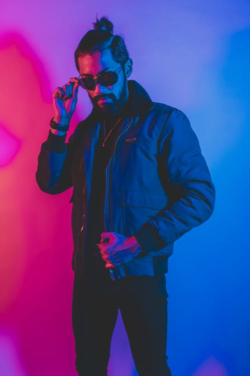 Serious bearded guy in trendy outfit and sunglasses standing in neon studio with blue and pink lights near wall