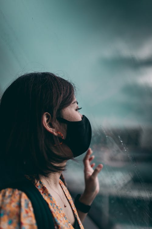 Unrecognizable woman in mask near window with raindrops