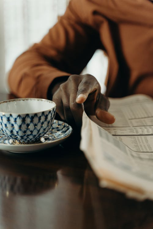 Person Holding White and Blue Floral Ceramic Teacup