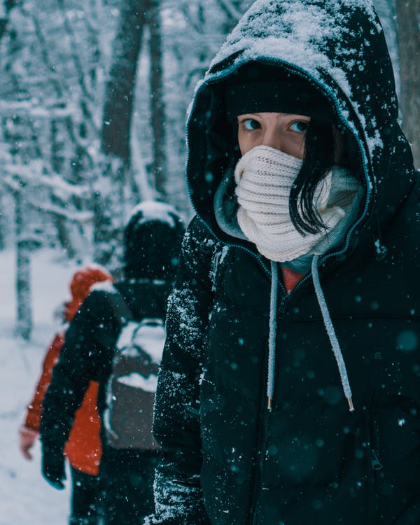 Person in Black and White Hoodie Covering Eyes With White Snow