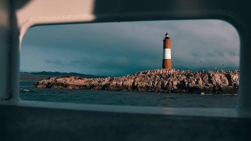 Biało Czarna Latarnia Morska Na Brązowym Skalistym Brzegu Pod Błękitnym Niebem