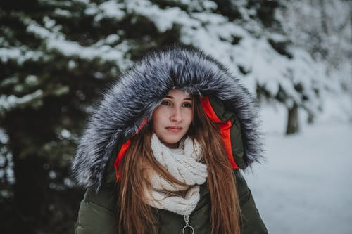 Serious woman in warm knitted scarf and outerwear standing near fir trees covered with snow in winter