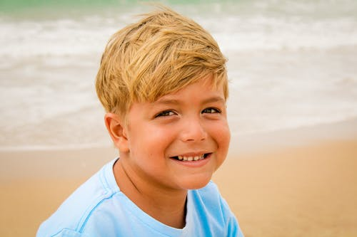 Joyful little boy relaxing on sandy seacoast during summer vacation