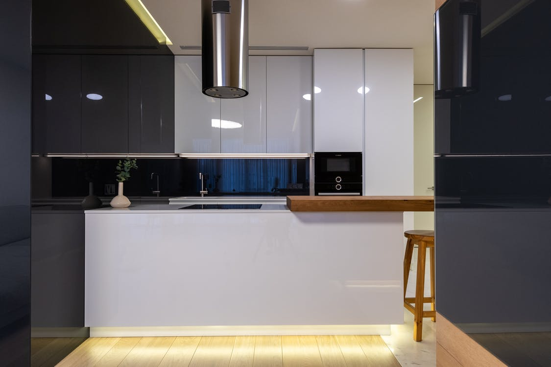 Interior of stylish kitchen with counter and appliances with cabinets glossy reflecting surface