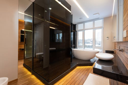 Stylish interior of bathroom with glass shower cabin