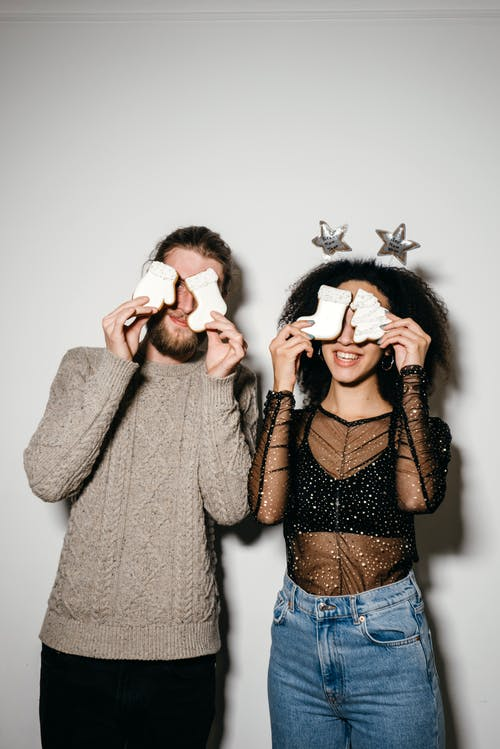 A Couple Covering Their Eyes with Sugar Cookies