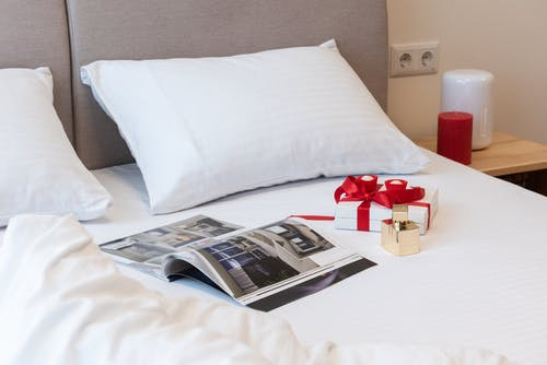Bed with opened magazine with gifts for celebration