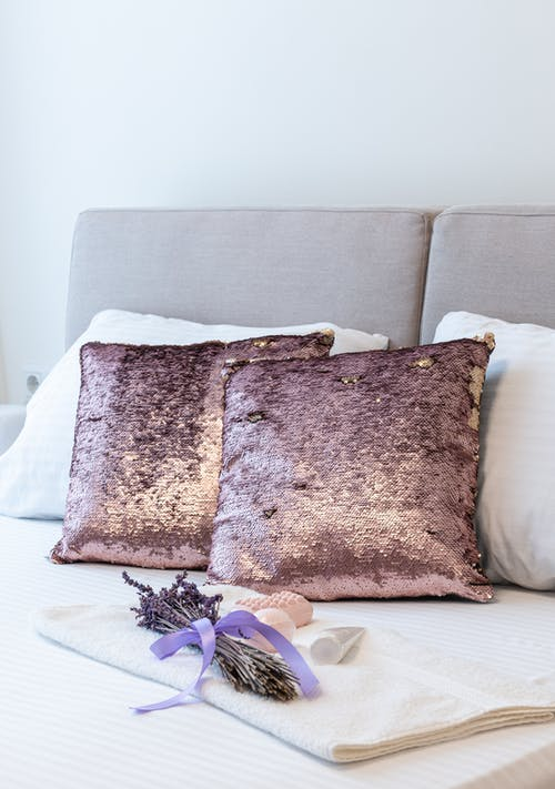 Cushions and bunch of lavender placed on soft bed covered with bed linens in bedroom