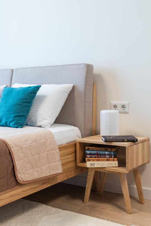 Interior of bedroom with bedside table with books