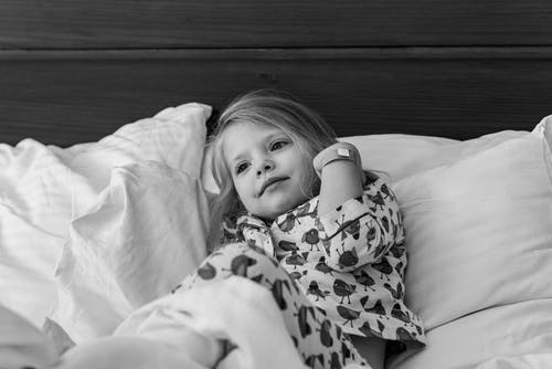 Black and white of adorable little girl in pajama lying on bed with soft pillows and looking away in sunny morning