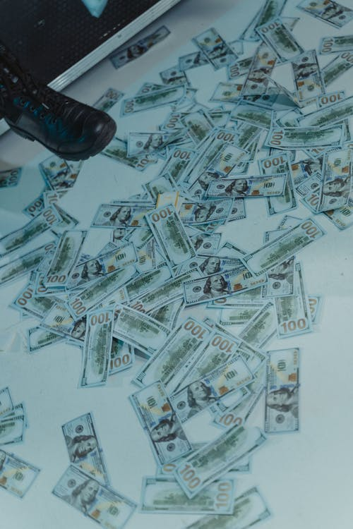US Dollar Paper Bills Scattered on White Surface