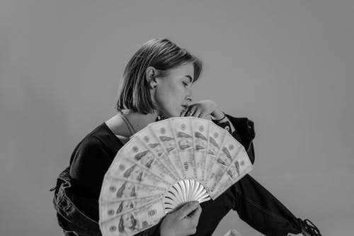 Woman Holding Hand Fan Made of Paper Money