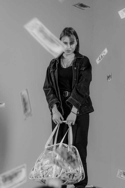 Woman in Black Jacket Holding Transparent Bag