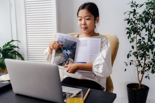 Girl Holding Book in Front of Silver Laptop