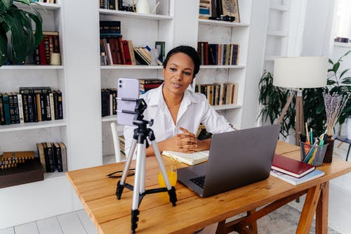 Woman in White Shirt Sitting at Desk with Silver Laptop and Smartphone