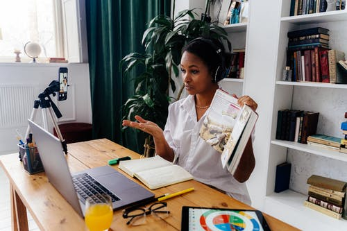 Woman Sitting in Front of Laptop Teaching Online