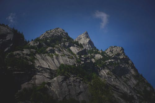 From below of massive rocky mountain with sharp peaks against blue sky in evening