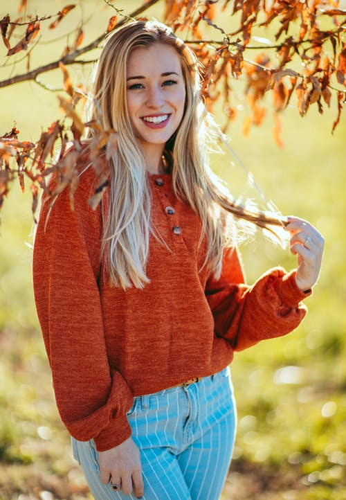 Beautiful cheerful female in warm sweater touching hair and looking at camera with charming smile while standing on sunny autumn park on autumn day