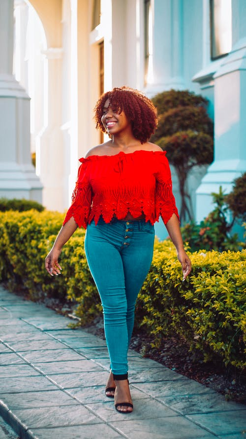 Woman in Red Off Shoulder Shirt and Blue Denim Jeans Standing on Gray Concrete Pavement during