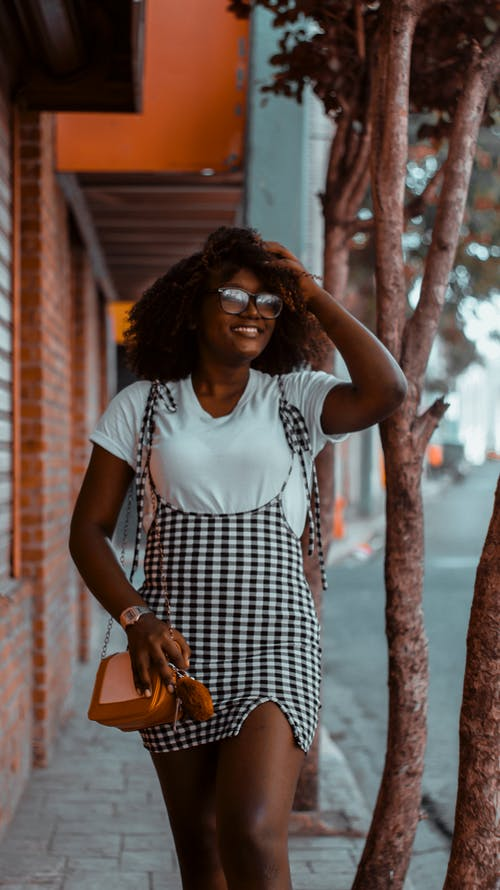 Woman in White and Black Checked Sleeveless Dress Wearing Sunglasses Standing Near Brown Wooden Wall during