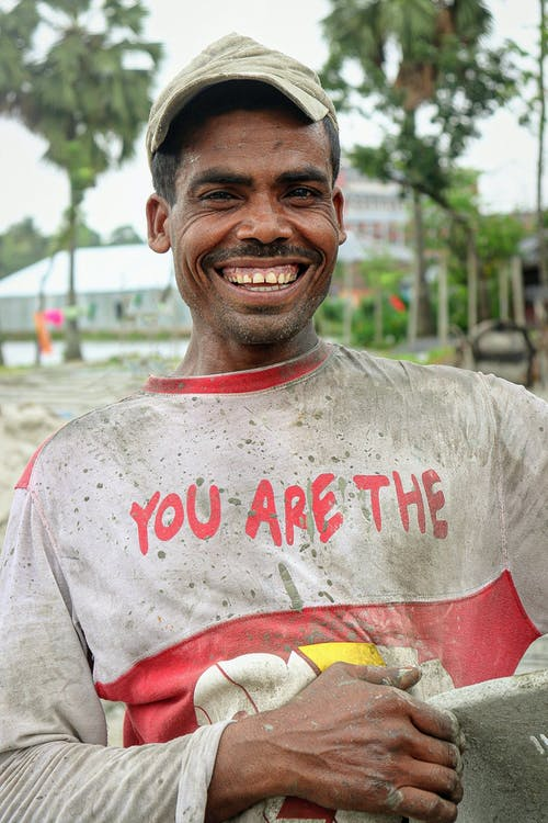Smiling ethnic man in dirty clothes working on sandy seashore