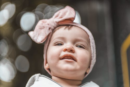 From below of positive little baby wearing pink headband with bow looking away on street against blurred background with bokeh
