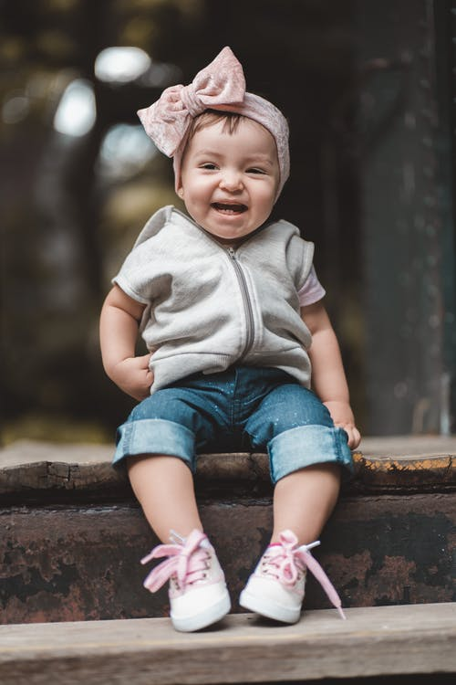 Full length adorable laughing little girl wearing stylish clothes and headband sitting on shabby wooden stairs in summer park