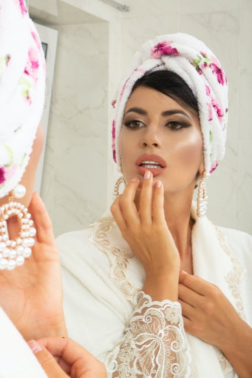 Charming female in turban on head looking at mirror and making makeup in light room in apartment