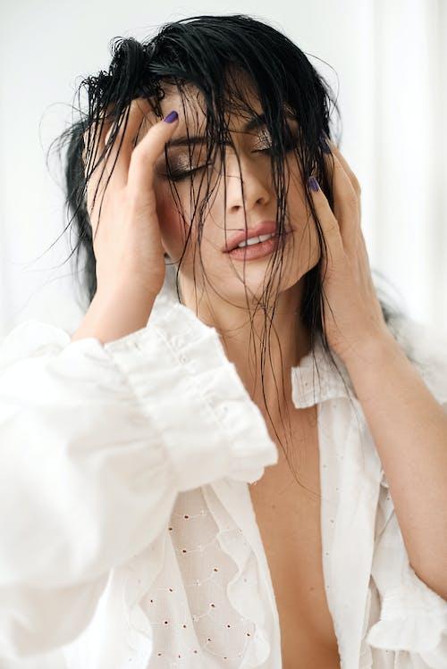 Donna In Camicia Di Vestito Bianca Che Copre Il Viso Con I Capelli