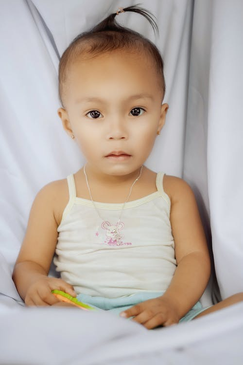 Cute baby girl sitting on white sheets with rattle