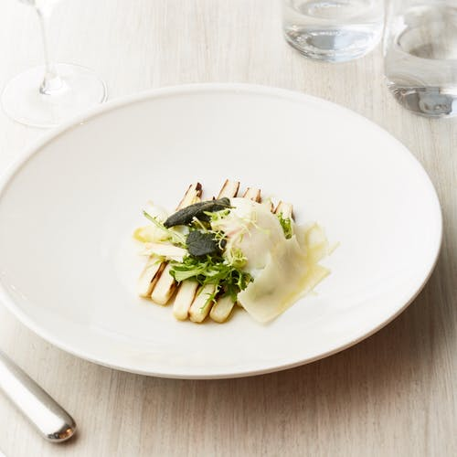 Appetizing dish with poached egg and zucchini served on plate with truffle and herbs