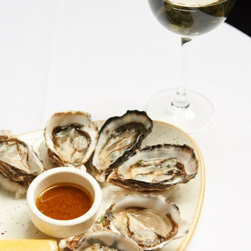 From above of raw oysters served on plate with sauce and lemon and placed on table with glass of white wine in restaurant