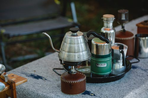 High angle of metal coffee kettle placed on small portable camping gas stove near various utensils on table in nature