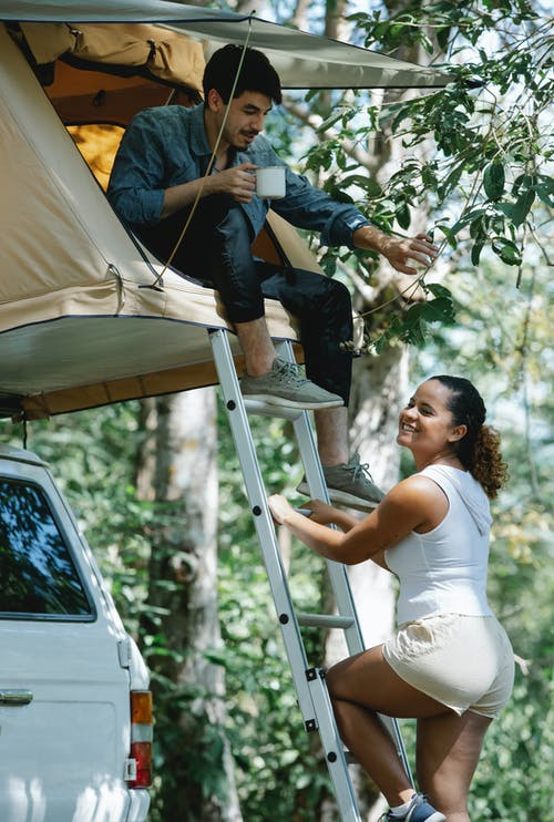 Side view of happy young Hispanic female traveler in casual clothes smiling while climbing ladder towards boyfriend drinking coffee in tent placed on car roof during camping in nature
