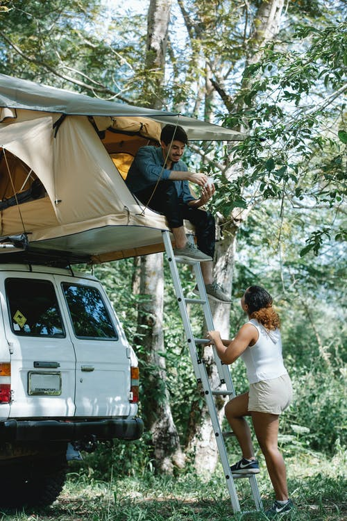 Side view of unrecognizable female camper going upstairs towards boyfriends sitting in tent placed on SUV car roof during road trip in forest on sunny summer day