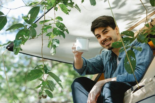 Positive young bearded male camper in casual clothes smiling and raising mug of aromatic coffee while relaxing in tent on sunny day in green forest