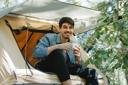 Happy young male camper drinking coffee in tent