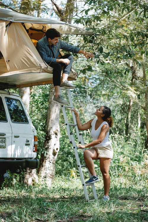 Young multiracial couple communicating during camping in nature