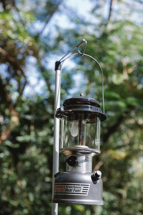 Vintage paraffin lamp hanging in woods during picnic