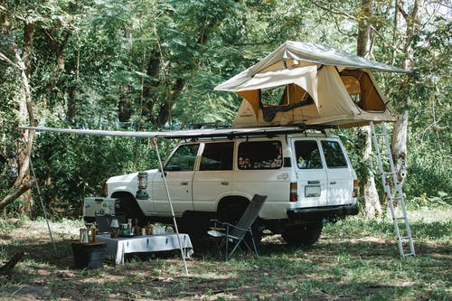 White off road car with camping tent on top parked in lush green forest near small table with various food and utensils during picnic on sunny day
