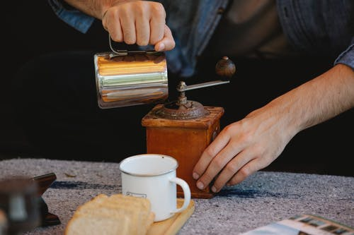 Crop unrecognizable male pouring water into manual coffee grinder placed on table before coffee brewing