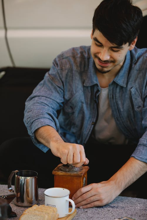 Crop content young man grinding coffee in manual grinder