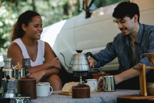 Young cheerful couple in casual wear boiling water in kettle on gas stove and grinding beans for coffee brewing while spending sunny day in camp