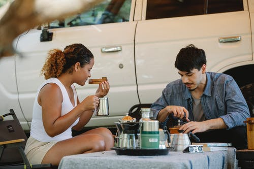 Multiethnic couple enjoying hot drinks and sandwiches in campsite