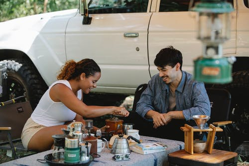 Cheerful young diverse couple in casual outfits grinding coffee and boiling water in gooseneck kettle while camping together in sunny nature
