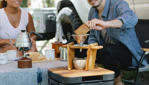 Crop smiling couple wearing casual outfits preparing aromatic pour over coffee during picnic on sunny day