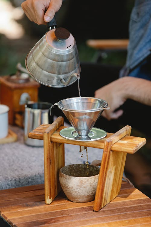 Crop faceless man pouring hot water into pour over filter