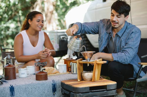 Content young man pouring hot water from gooseneck kettle into filter while preparing pour over coffee with smiling girlfriend during picnic