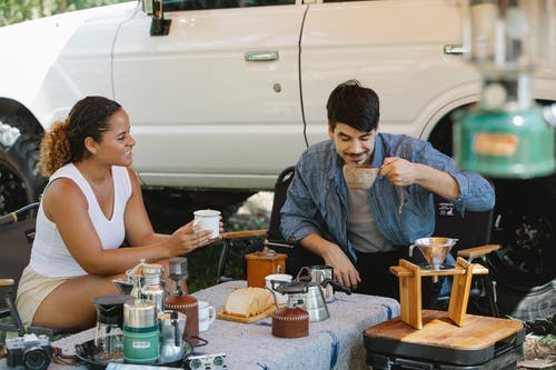 Positive diverse couple drinking delicious pour over coffee in campsite